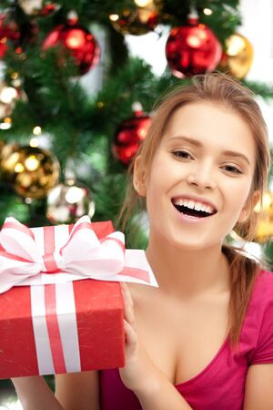 bright picture of happy woman with gift box and christmas tree Stock Photo - 15446053
