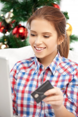 happy woman with laptop computer and credit card over christmas tree     Stock Photo - 15446077