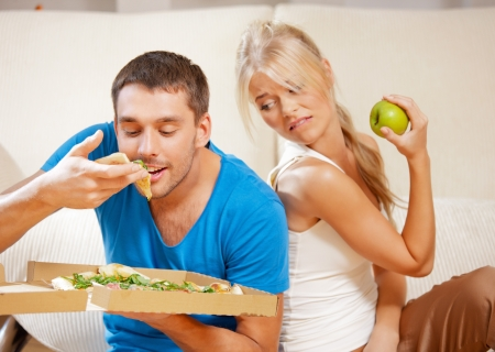 bright picture of couple eating different food  focus on man Stock Photo - 15452167