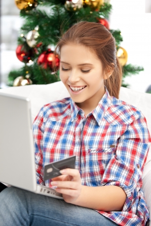 holiday spending: happy woman with laptop computer and credit card over christmas tree