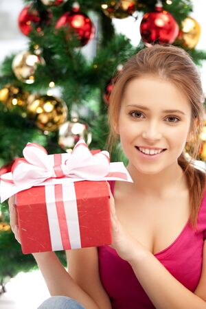 bright picture of happy woman with gift box and christmas tree Stock Photo - 15452180