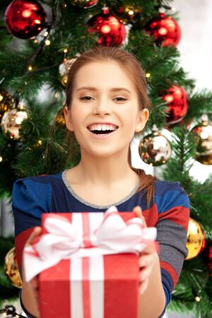 bright picture of happy woman with gift box and christmas tree       Stock Photo - 15452172
