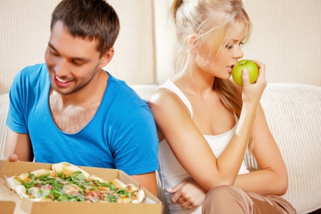 bad apple: bright picture of couple eating different food  focus on woman  Stock Photo
