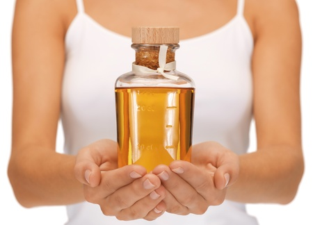 body oil: bright picture of female hands with oil bottle Stock Photo