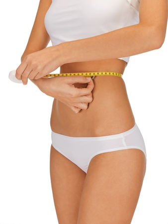 weightloss: closeup picture of woman with measure tape