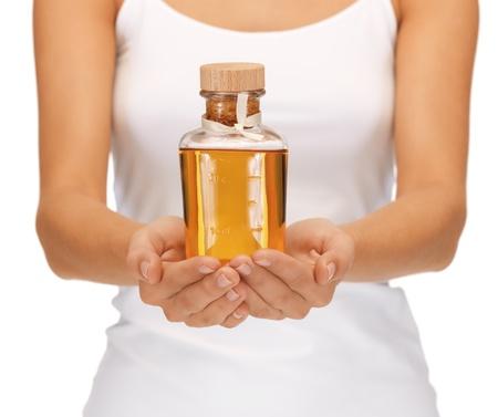 olio corpo: immagine luminosa di mani femminili con la bottiglia di olio Archivio Fotografico