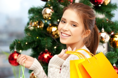 bright picture of happy woman with shopping bags and christmas tree      Stock Photo - 15691690
