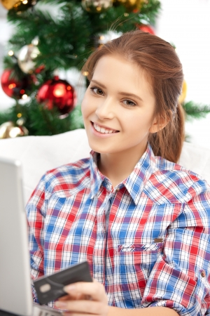 happy woman with laptop computer and credit card over christmas tree     Stock Photo - 15618735