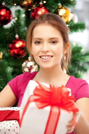 bright picture of happy woman with gift box and christmas tree Stock Photo - 15618716