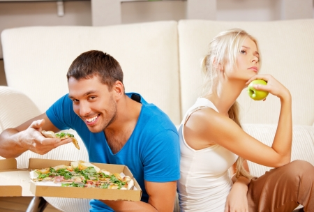 fatty food: bright picture of couple eating different food  focus on man  Stock Photo