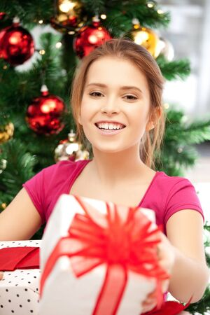 bright picture of happy woman with gift box and christmas tree       Stock Photo - 15692161