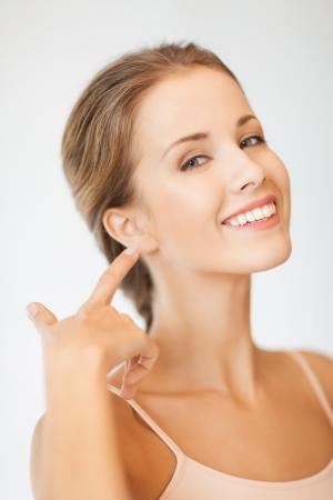 buen vivir: imagen de hermosa mujer apuntando a oreja