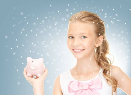 christmas savings: picture of lovely teenage girl with piggy bank