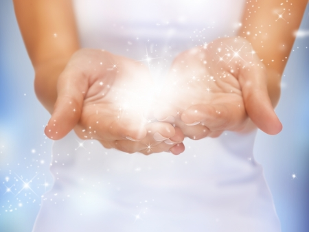 giving hands: bright closeup picture of magic twinkles on female hands Stock Photo