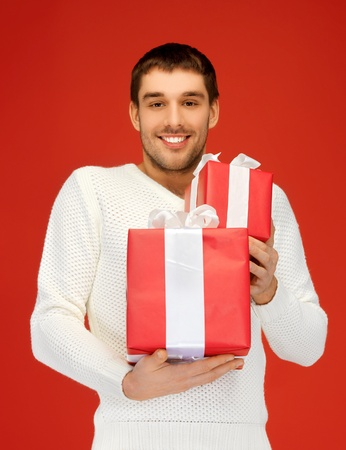 bright picture of handsome man holding many gift boxes  photo