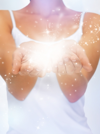 something: bright closeup picture of magic twinkles on female hands Stock Photo