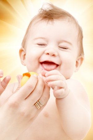portrait of laughing baby boy in mother hands playing with rubber duck photo