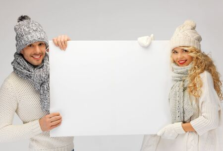 picture of family couple in a winter clothes holding blank board Stock Photo - 16142100