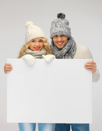 picture of family couple in a winter clothes holding blank board Stock Photo - 16165307