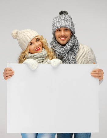 picture of family couple in a winter clothes holding blank board Stock Photo - 16216117
