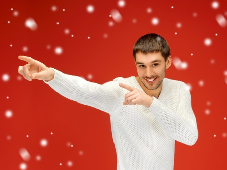 handsome man in warm sweater pointing his finger  Stock Photo - 16216068