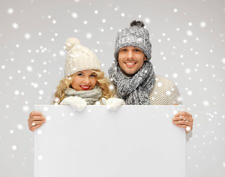 tog: picture of family couple in a winter clothes holding blank board Stock Photo