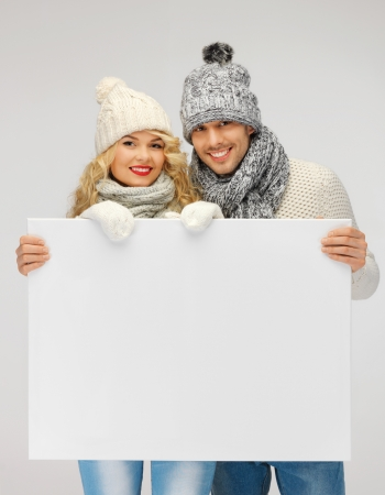 head wear: picture of family couple in a winter clothes holding blank board Stock Photo