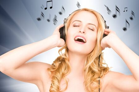 blonde females: picture of happy woman in headphones with notes Stock Photo