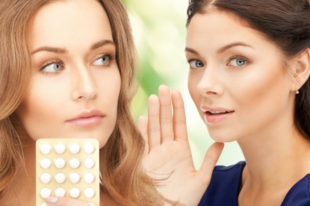 birth prevention: picture of young beautiful women with pills Stock Photo