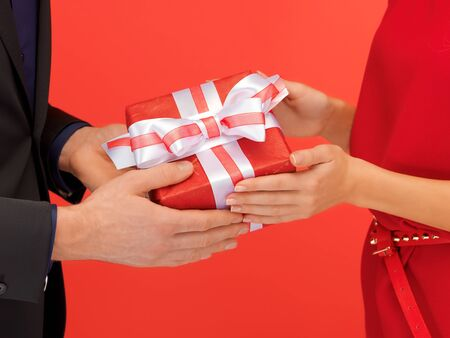 closeup picture of man and woman s hands with gift box photo