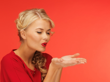 girl blowing: lovely woman in red dress blowing something on the palms of her hands Stock Photo