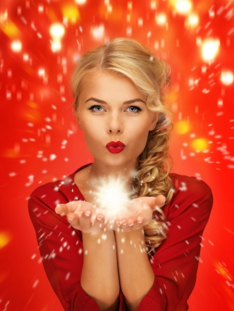 something: lovely woman in red dress blowing something on the palms of her hands Stock Photo