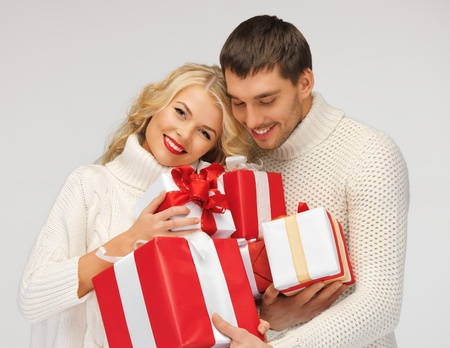 picture of romantic couple in a sweaters with gift boxes photo