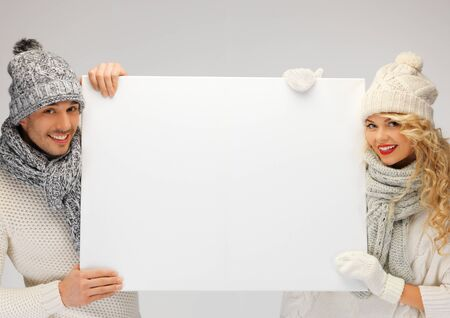 picture of family couple in a winter clothes holding blank board Stock Photo - 16549369