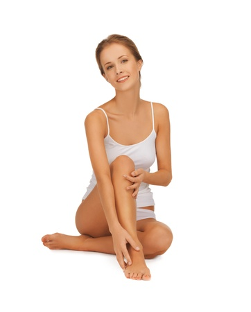 bare feet girl: picture of beautiful woman in cotton undrewear touching her legs Stock Photo