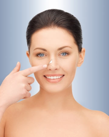 picture of beautiful woman pointing to nose photo
