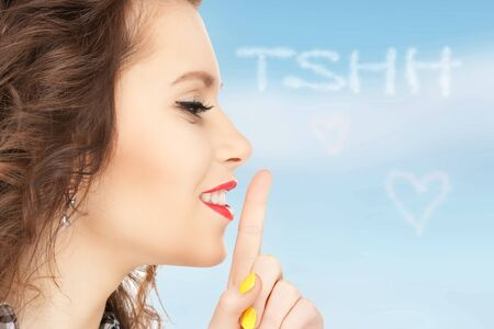bright picture of young woman with finger on lips Stock Photo - 16619176