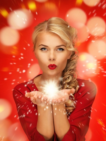 lovely woman in red dress blowing magic on the palms of her hands photo