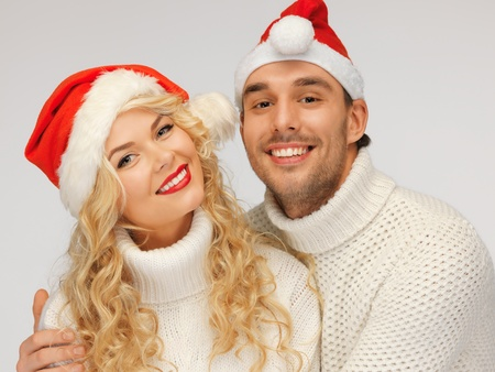santa helper: picture of family couple in sweaters and santa s hats Stock Photo