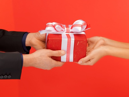 wrapped present: closeup picture of man and womans hands with gift box Stock Photo