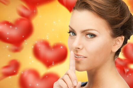 bright picture of young woman with finger on lips Stock Photo - 16673216