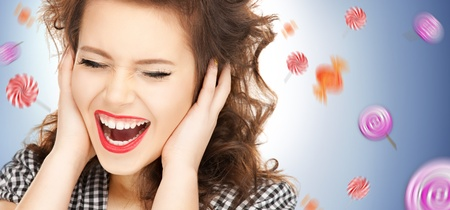 picture of woman with hands on ears and flying lollipops Stock Photo - 16673242