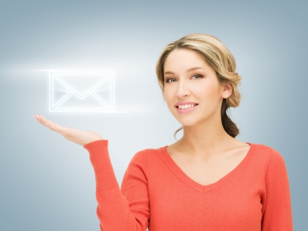 smiling woman showing virtual envelope on the palm of her hand photo