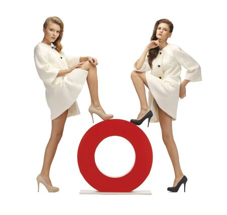 two lovely teenage girls in white coats with o letter photo