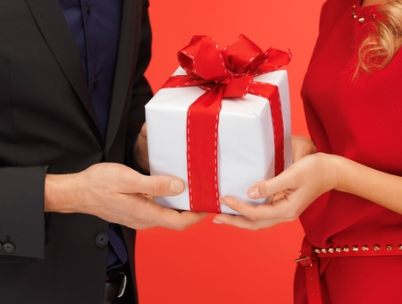birthday suit: closeup picture of man and woman s hands with gift box