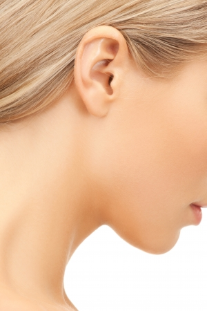 female face closeup: bright closeup picture of woman s ear Stock Photo