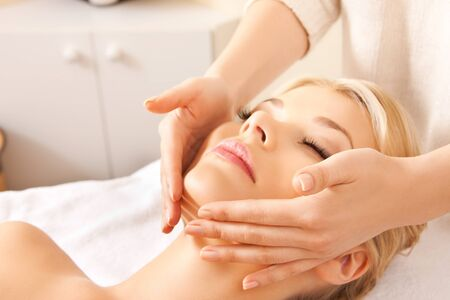 aging face: picture of calm beautiful woman in massage salon  focus on hands