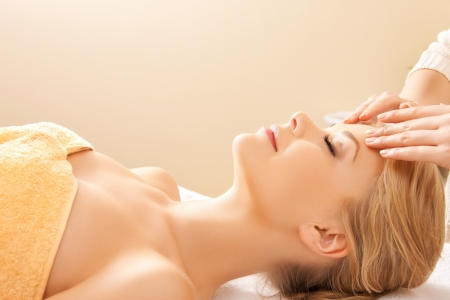 massage face: picture of happy beautiful woman in massage salon
