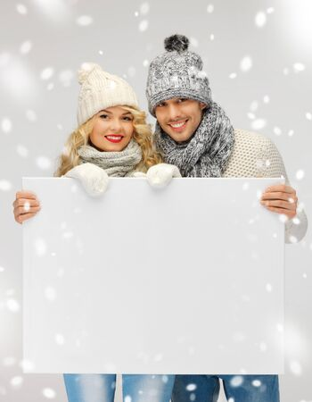 winter sweater: picture of family couple in a winter clothes holding blank board Stock Photo