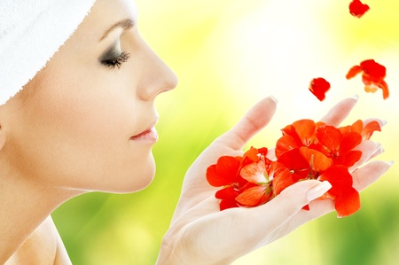 lovely woman with red flower petals in spa